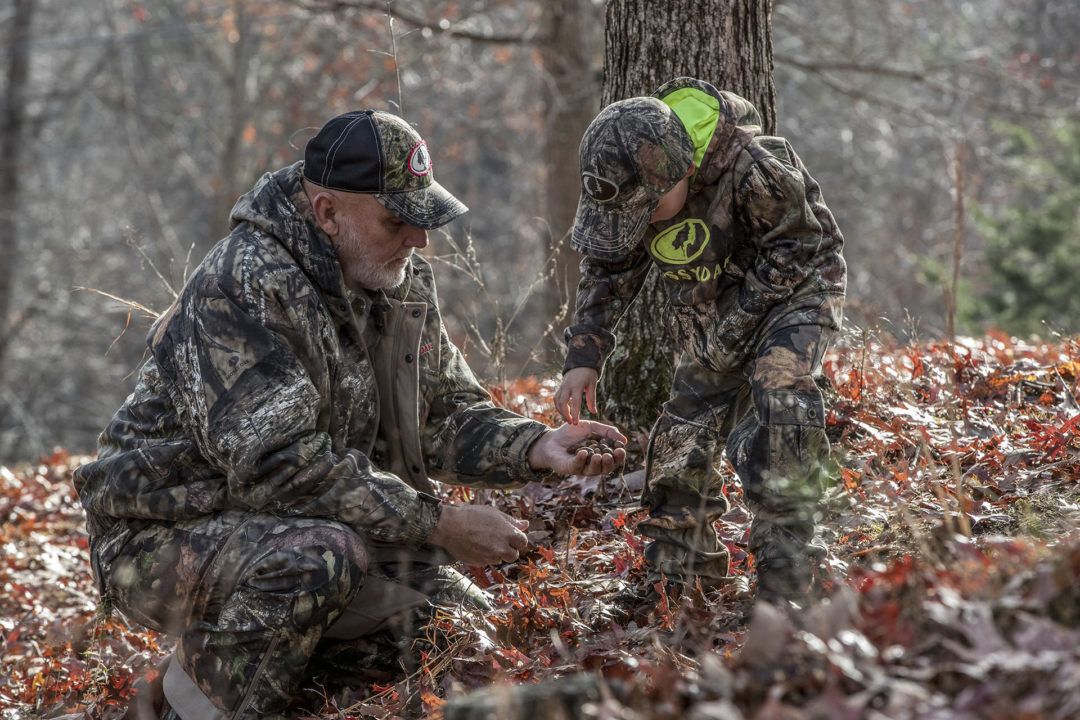 Grandfather teaching grandson about wildlife in Mossy Oak Brand Camo.